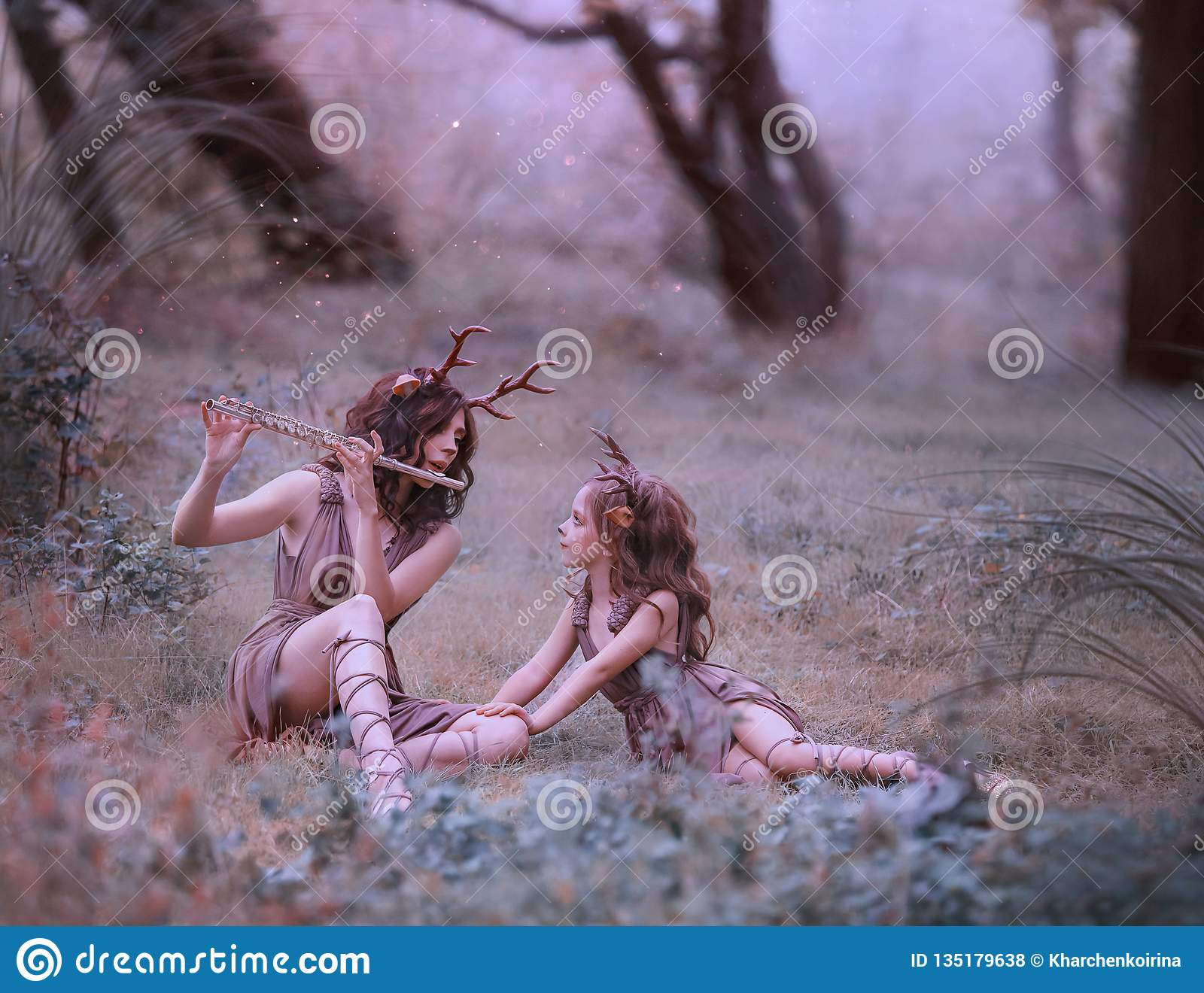 Creative fabulous family shooting, faun mom plays lullaby on flute for her child, fairytale characters deer in long