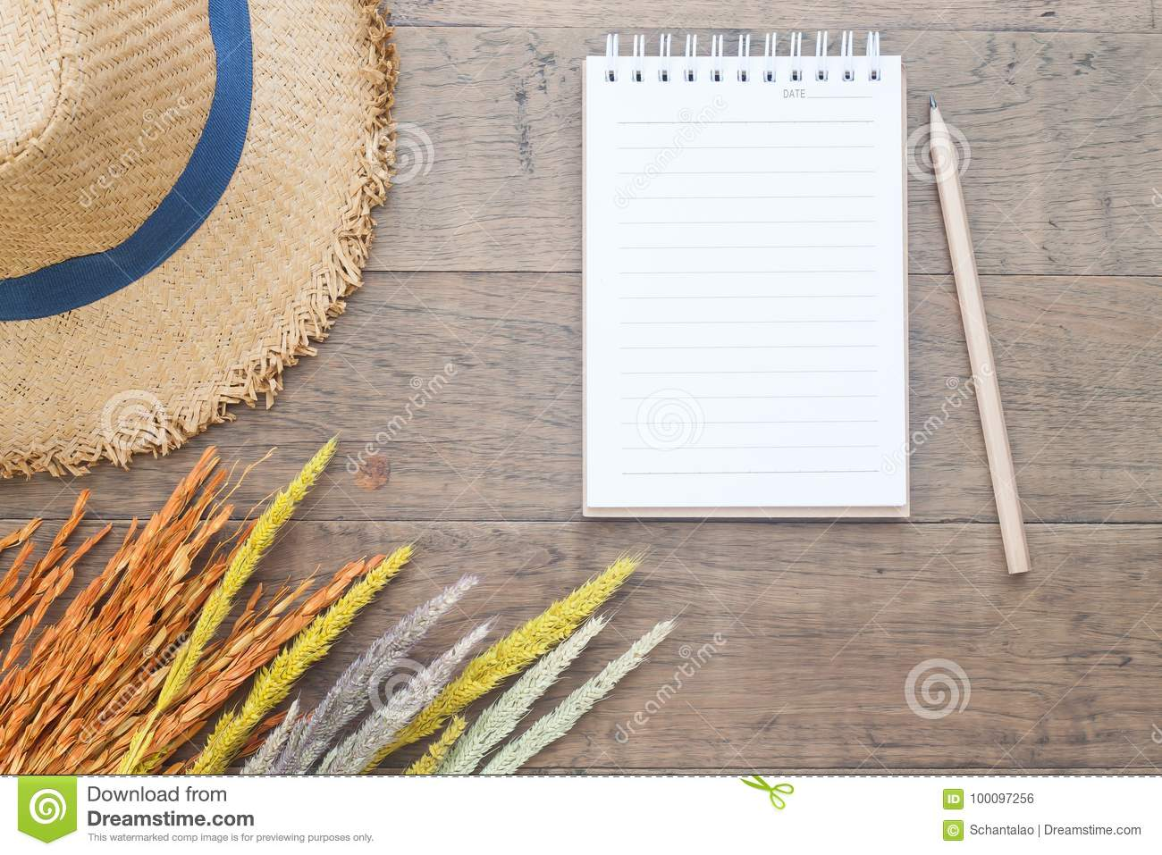 Creative flat lay of Autumn and Fall concept, Dried flowers, straw hat and blank notebook with pencil on wooden