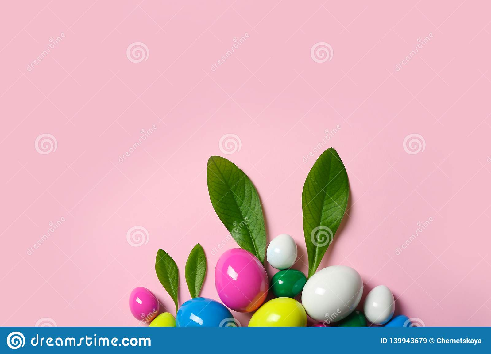 Creative flat lay composition with Easter bunny ears made of green leaves and eggs on color background