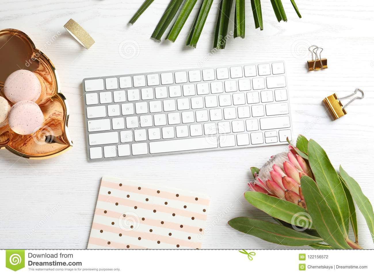 Creative flat lay composition with tropical flower, macaroons and computer keyboard