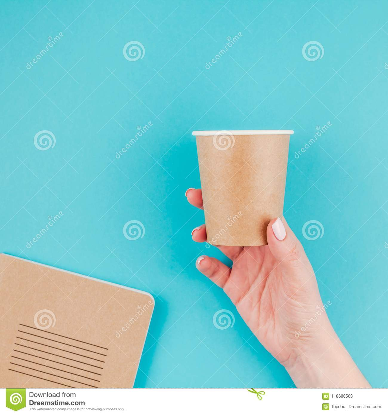 Creative Flat Lay Of Woman Hand Holding Craft Paper Coffee Cup And Notebook Diary With Copy Space On Turquoise Background In Minimalism Style