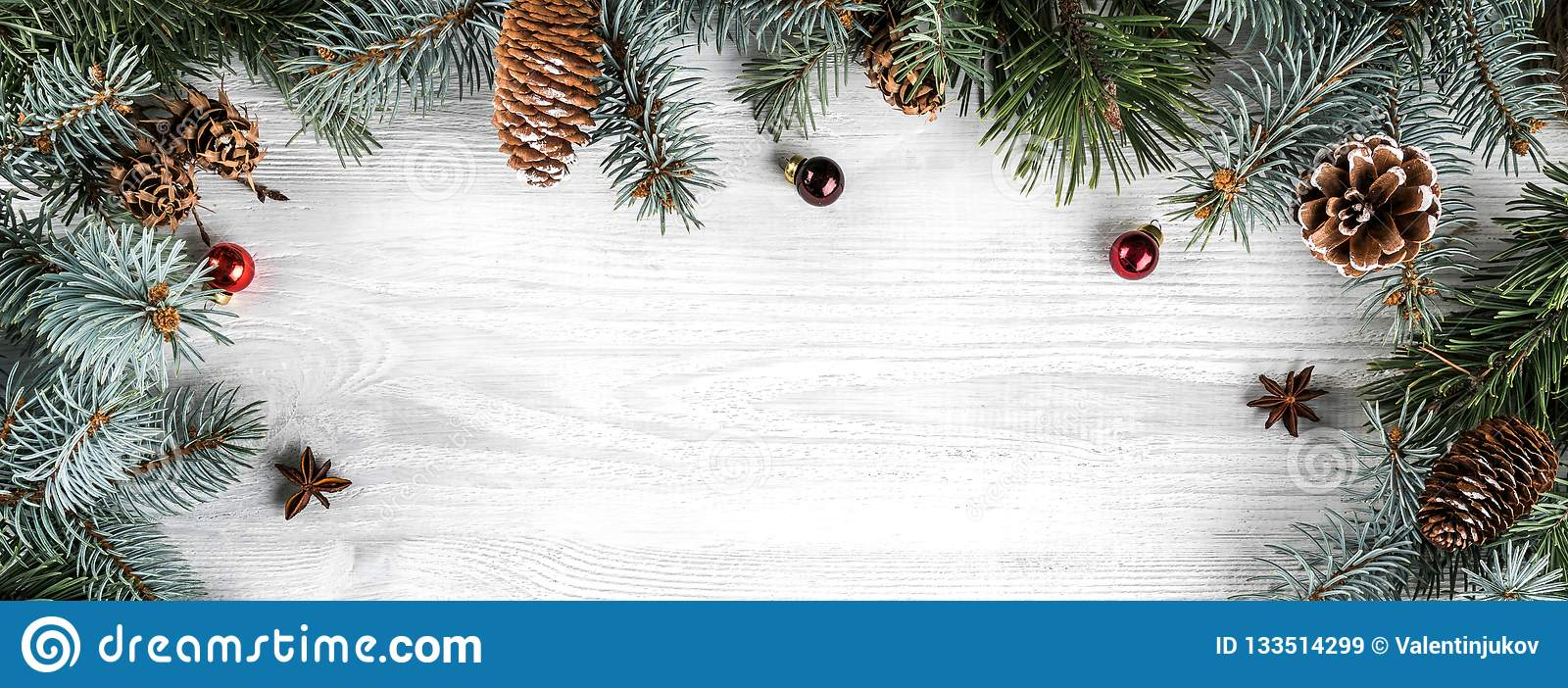 Creative frame made of Christmas fir branches on white wooden background with red decoration
