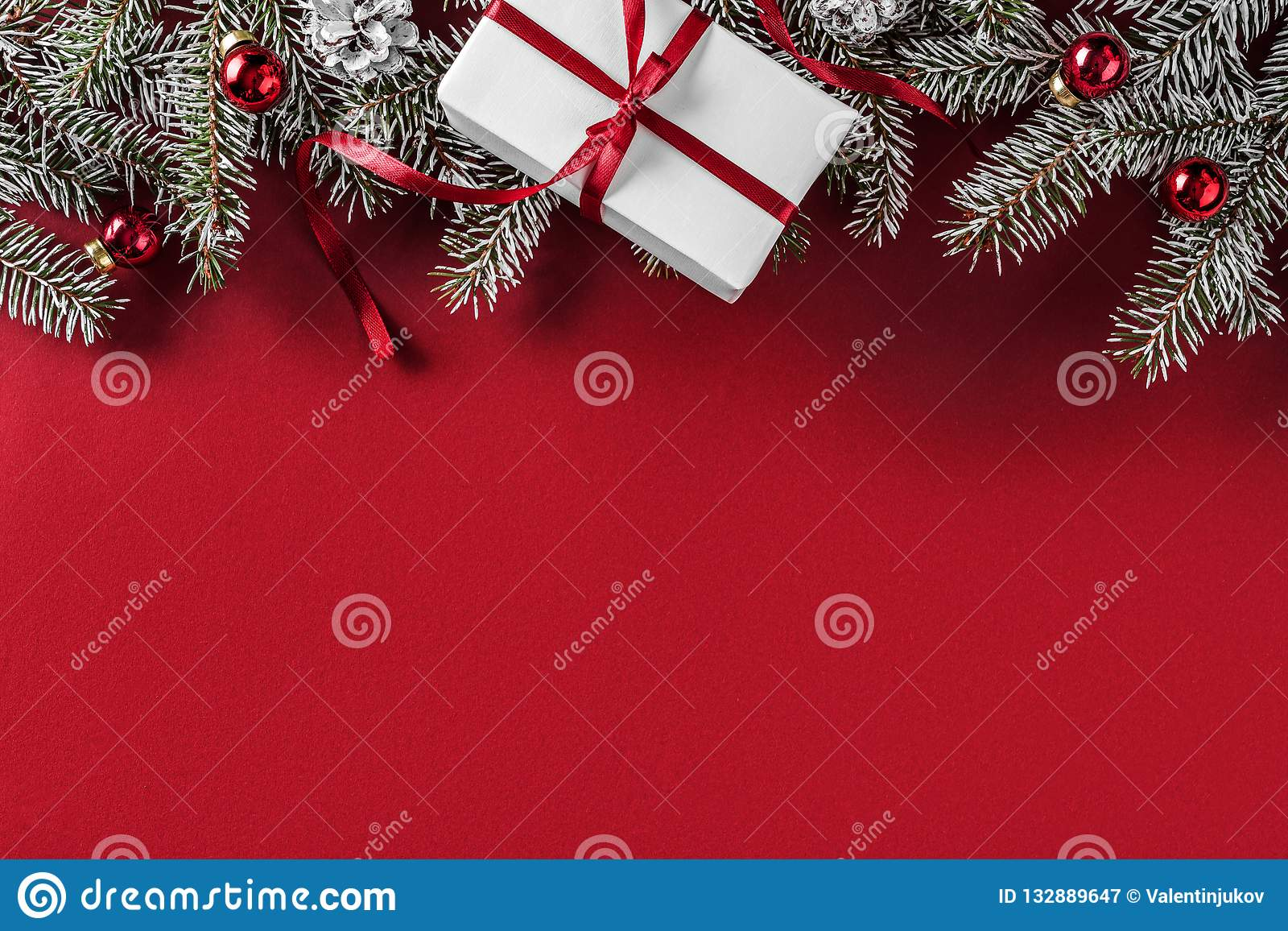 Creative layout frame made of Christmas fir branches, pine cones, gifts, red decoration on red background.
