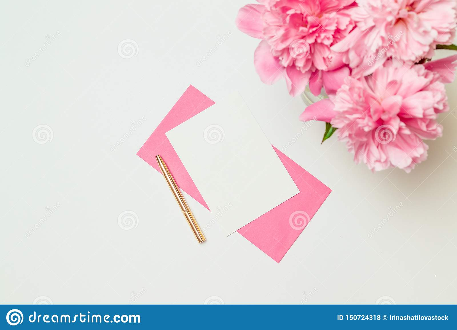 Creative layout made of pink paper envelope with a gold pen, a bouquet of pink peonies isolated on white background
