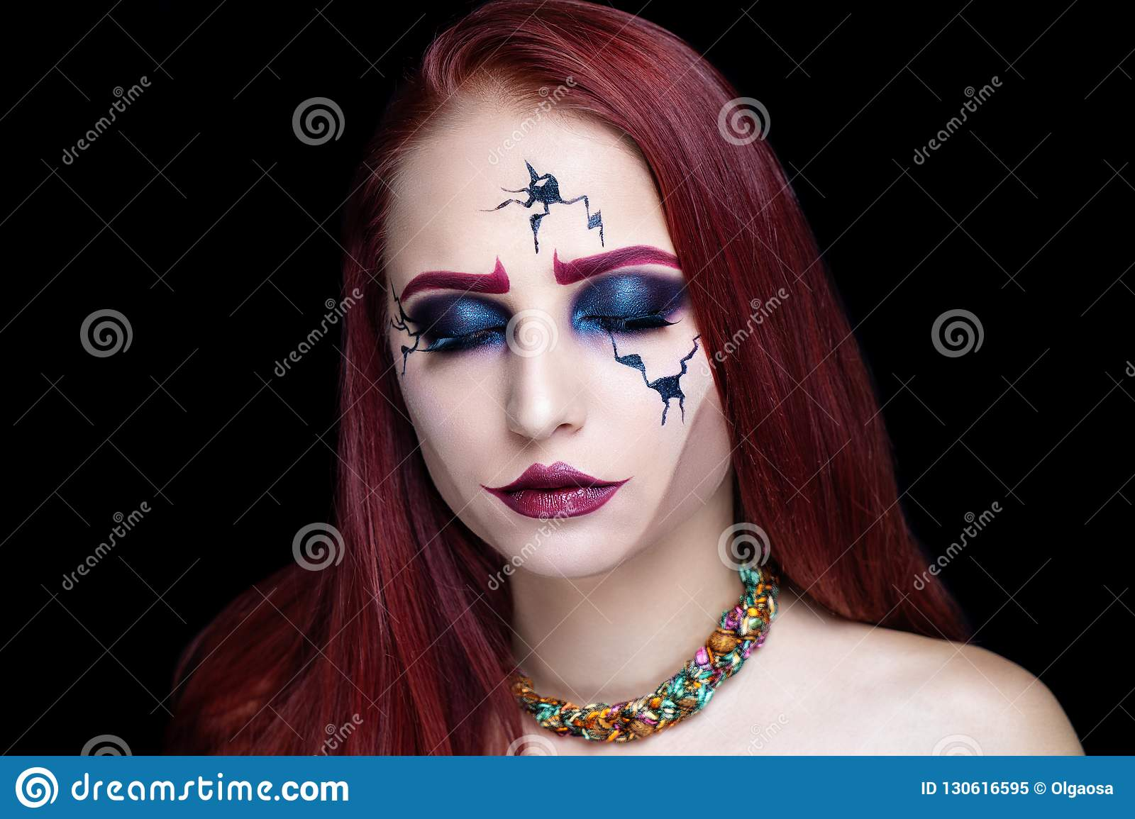 Creative makeup for Halloween party, black lines of cracks on model face. Sad eyes with blue shadows, hard intensive contouring cheekbones.