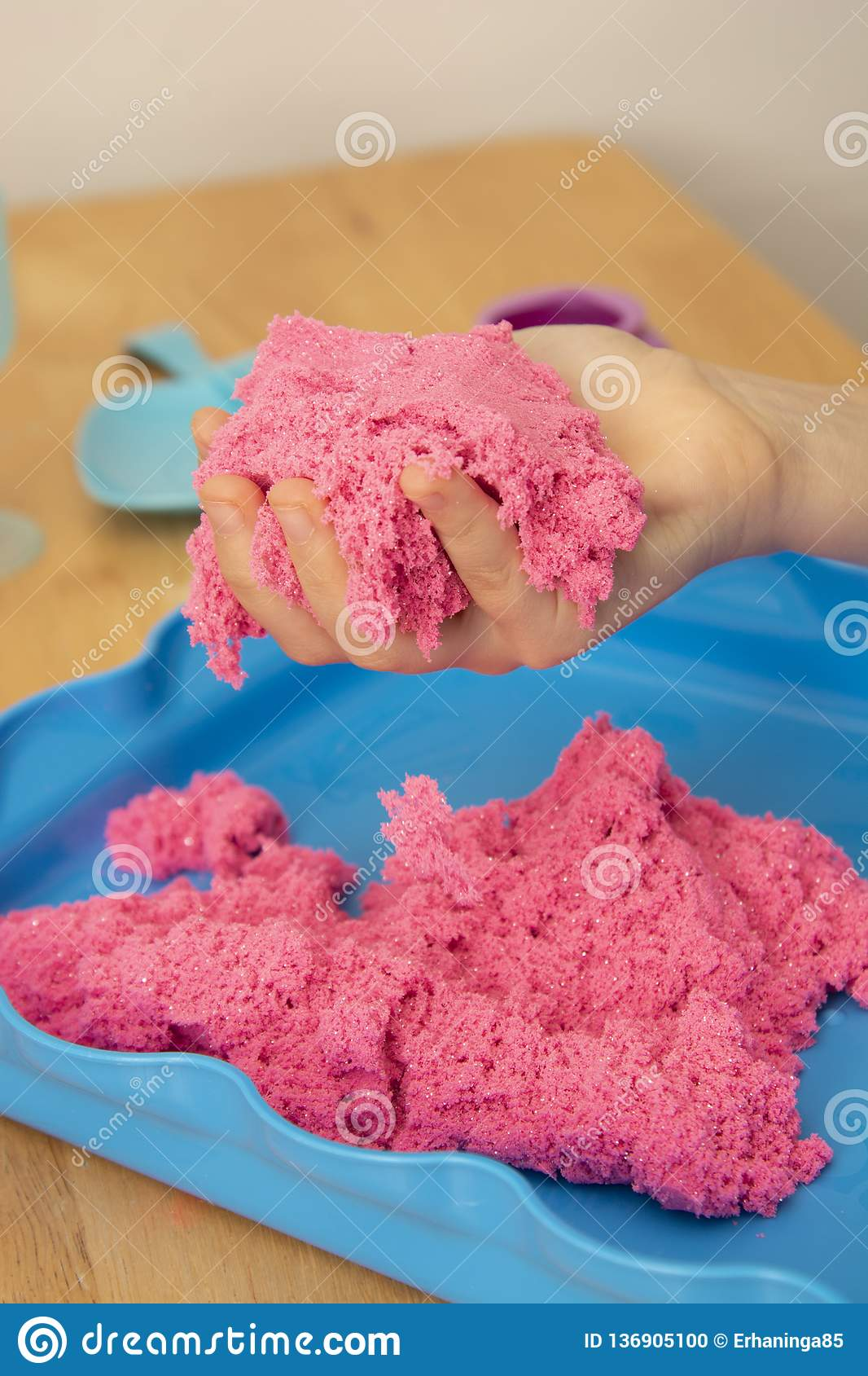 Creative play for children. Education and parenting. Children playing with pink kinetik sand