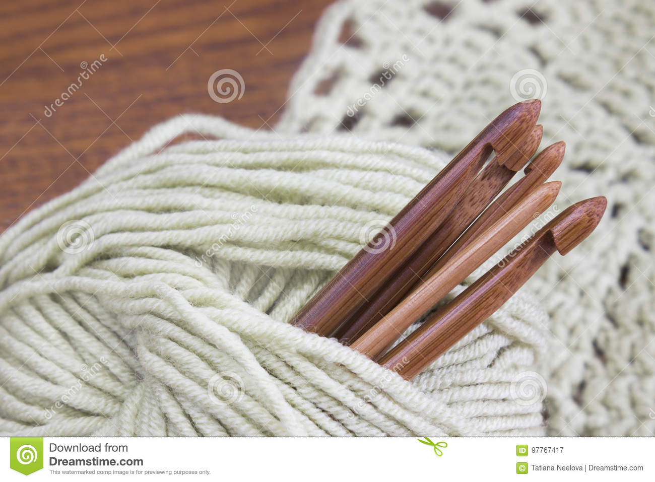 Creative work place for homemade crafts. Wooden natural bamboo crochet hooks, doily and yarn ball on the table.