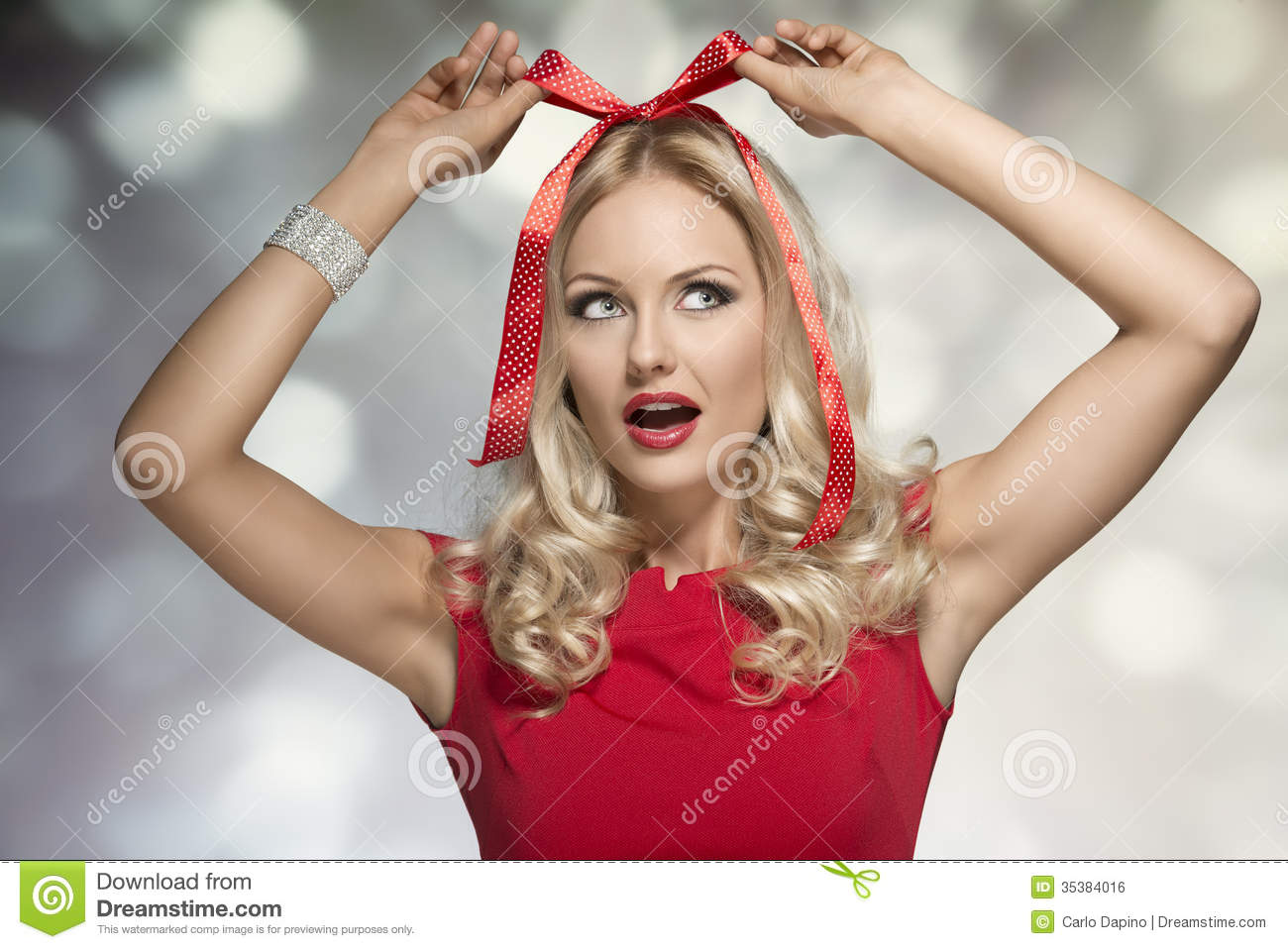 Woman adorned like a christmas present with bow on her head wearing