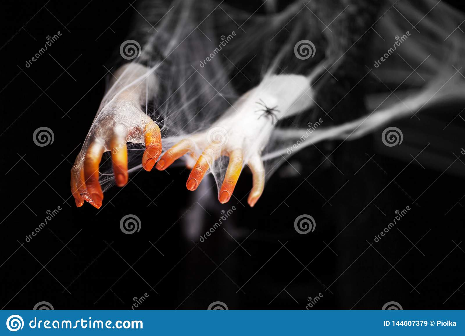 Creepy halloween hand in orange and white with spider web, zombie hand