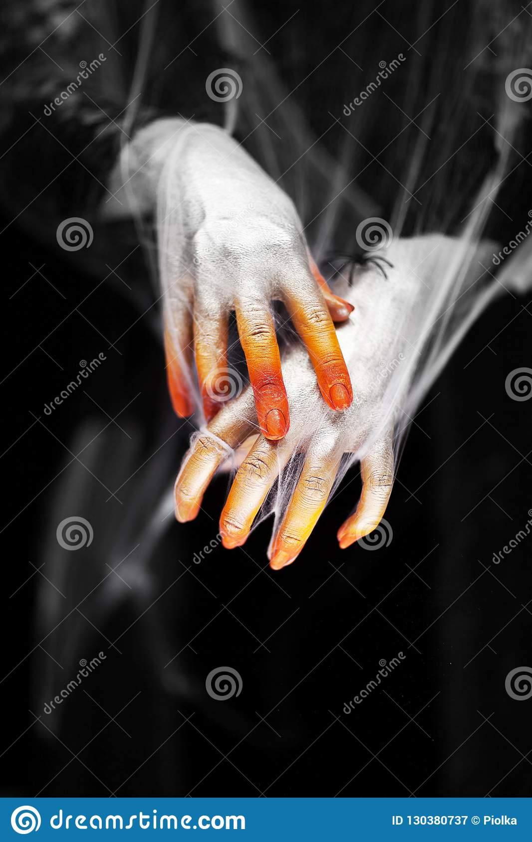 Creepy halloween hands with red, orange and silver covered in a spider web with spiders
