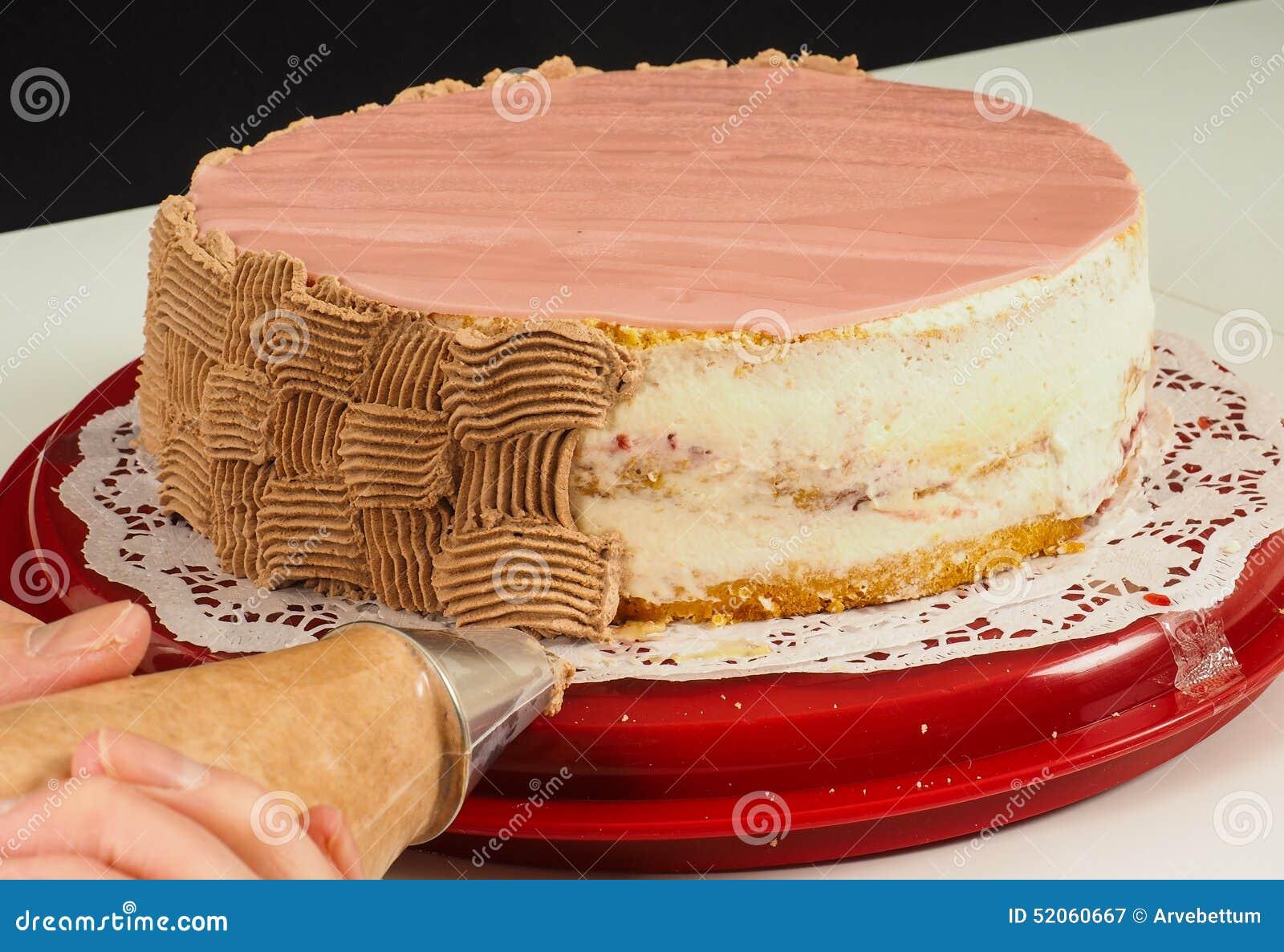 Crema aflautada del chocolate del panadero profesional de la torta sobre la torta