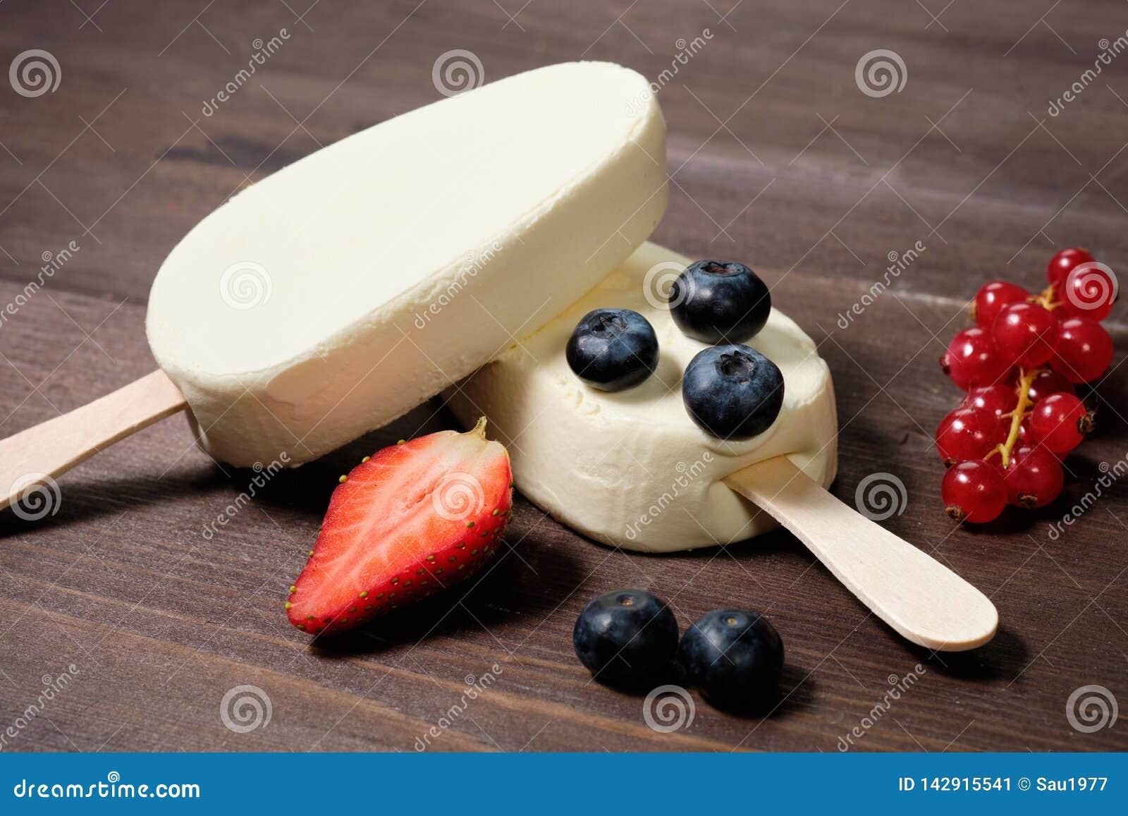 Crema bianca del gelato alla crema su un bastone con le fragole, i mirtilli ed il ribes rosso sui precedenti di legno del dack
