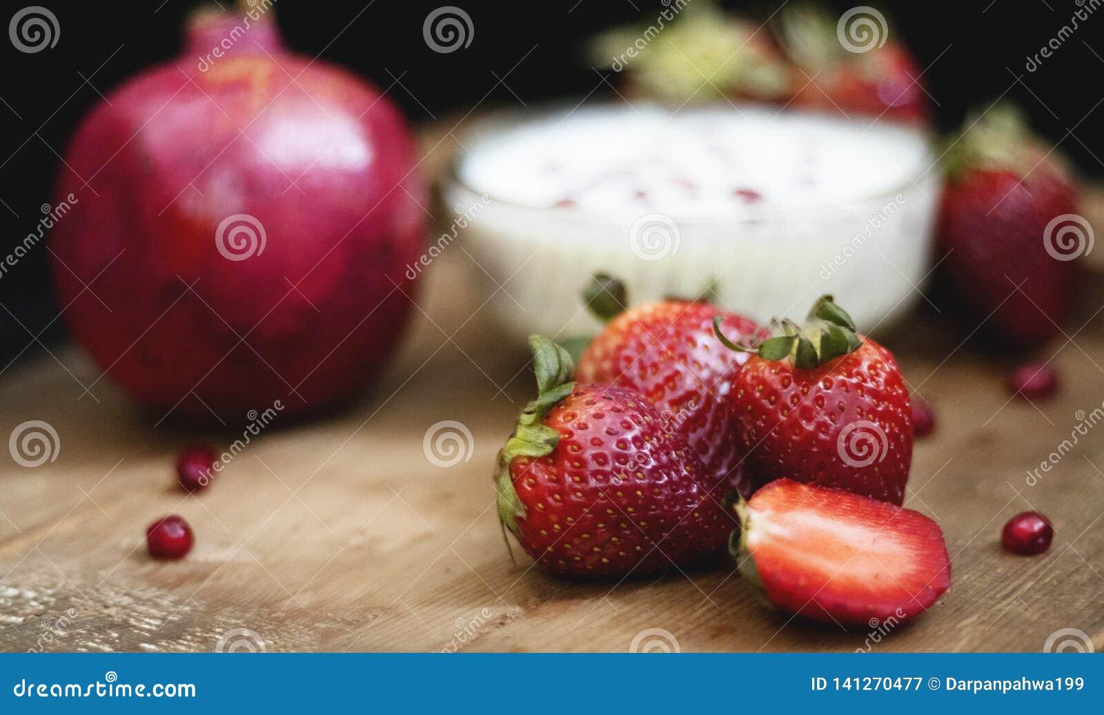 Crema della frutta sul bordo di legno con il melograno ed altre fragole in un fondo scuro