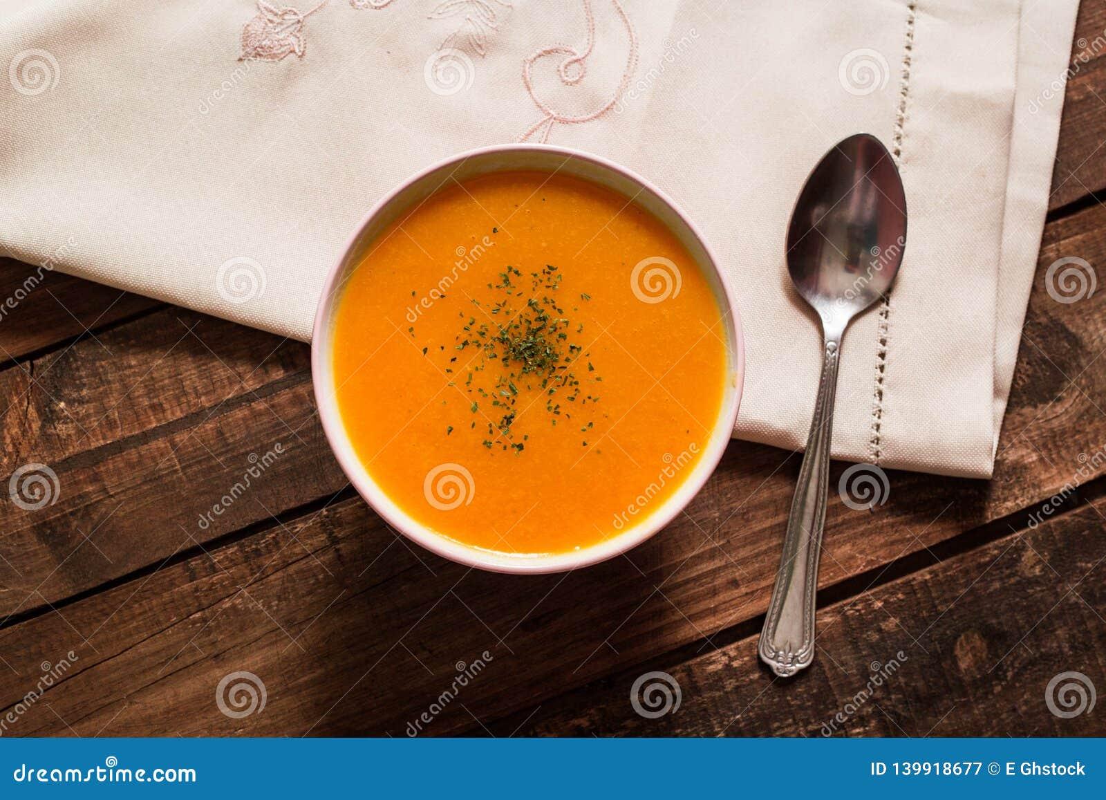Crema della zucca con la erba cipollina ed il prezzemolo sulla tavola di legno