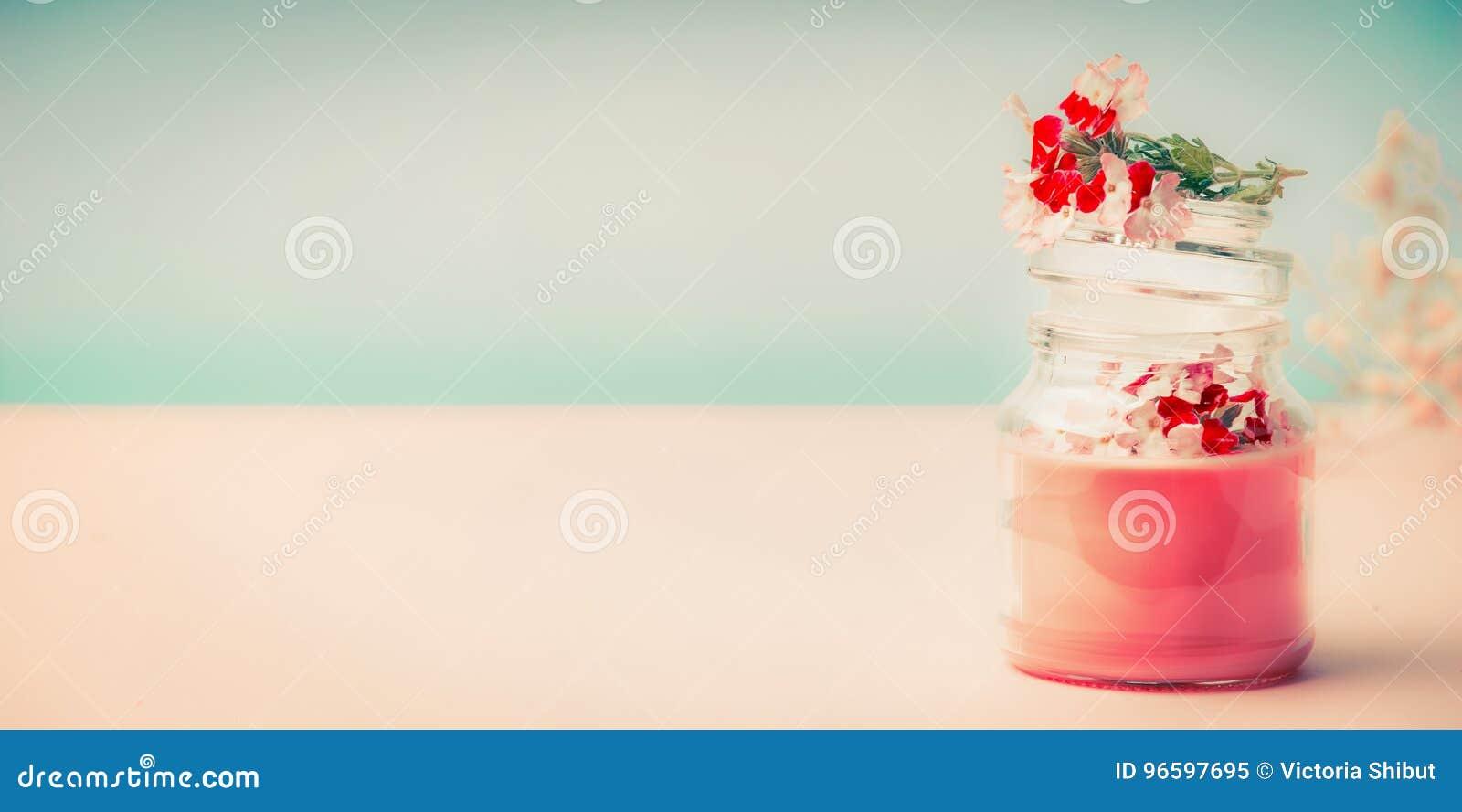 Crema rosada en el tarro de cristal para el cuidado de piel con los soportes de flores en la tabla en el fondo de la turquesa, vi