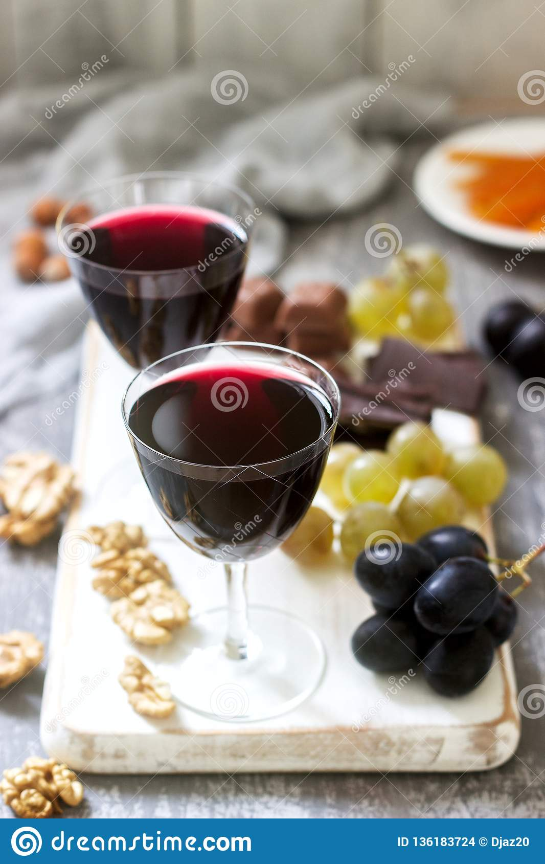 Creme de Cassis homemade liqueur served with grapes, nuts and chocolate. Rustic style.