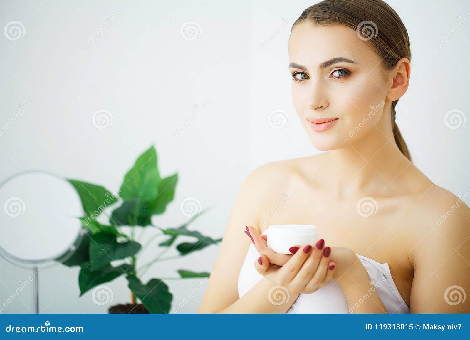 Creme do cosmético da posse da mulher Modelo bonito dos jovens da cara