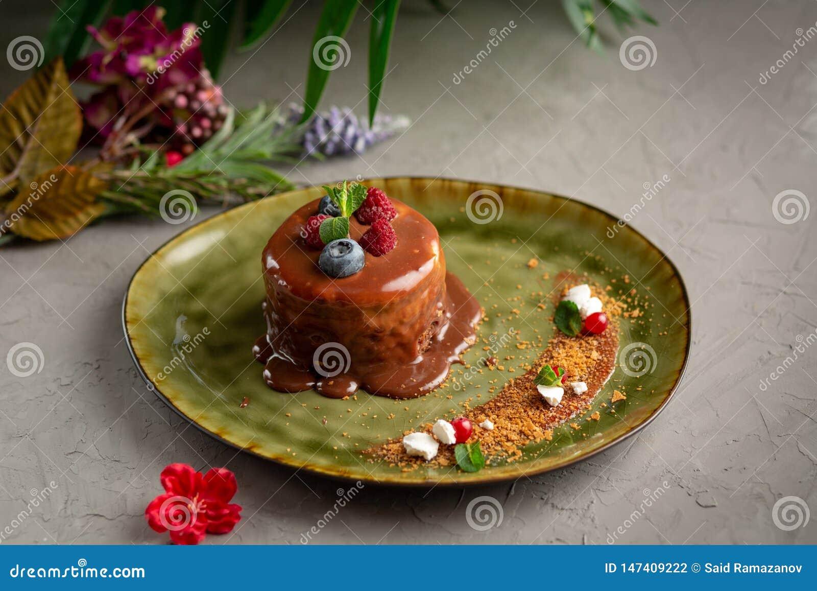 Crepe con el chocolate y las bayas derretidos en un fondo gris