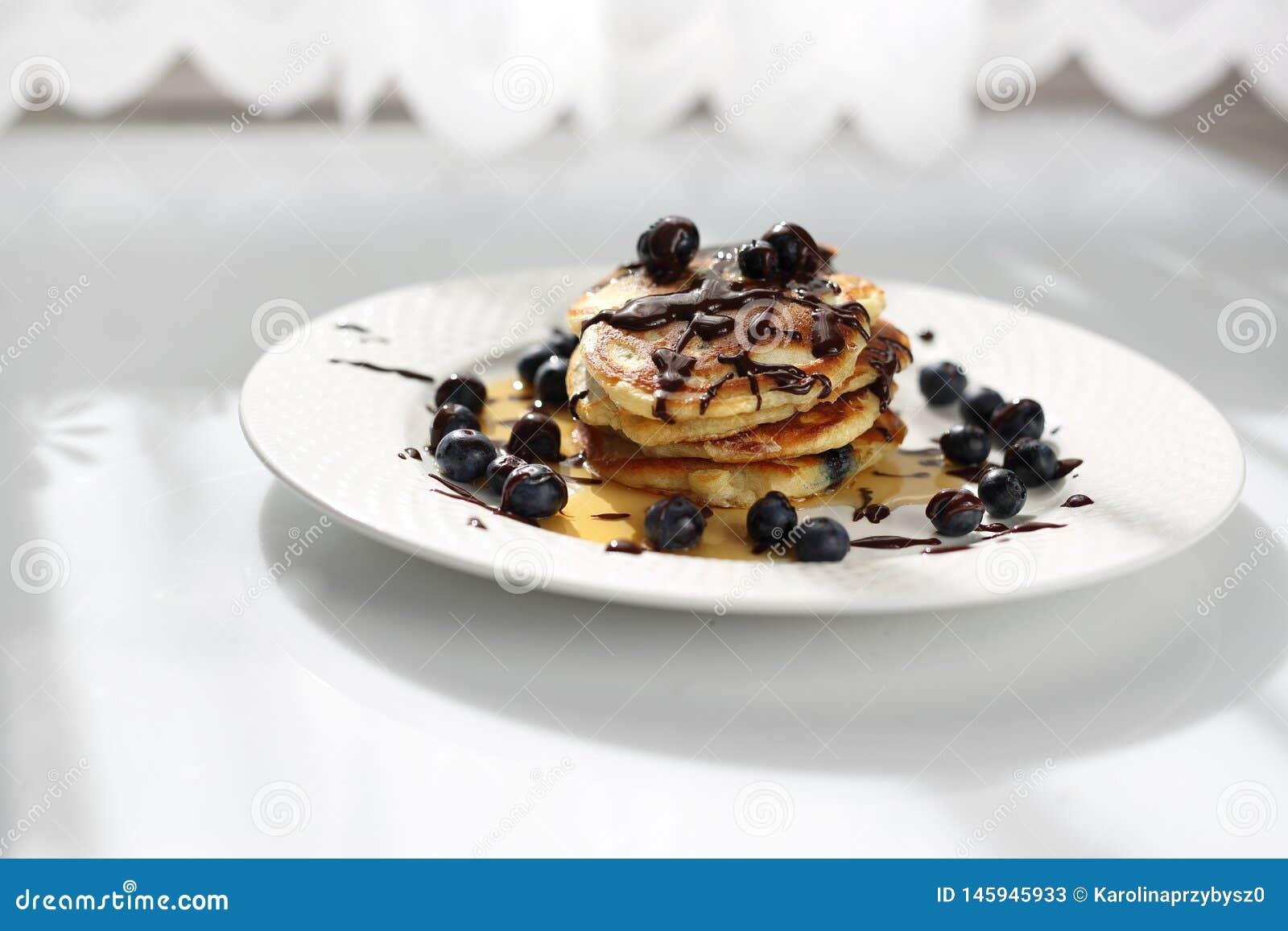 Crepes dulces del desayuno con los ar?ndanos y el jarabe de arce