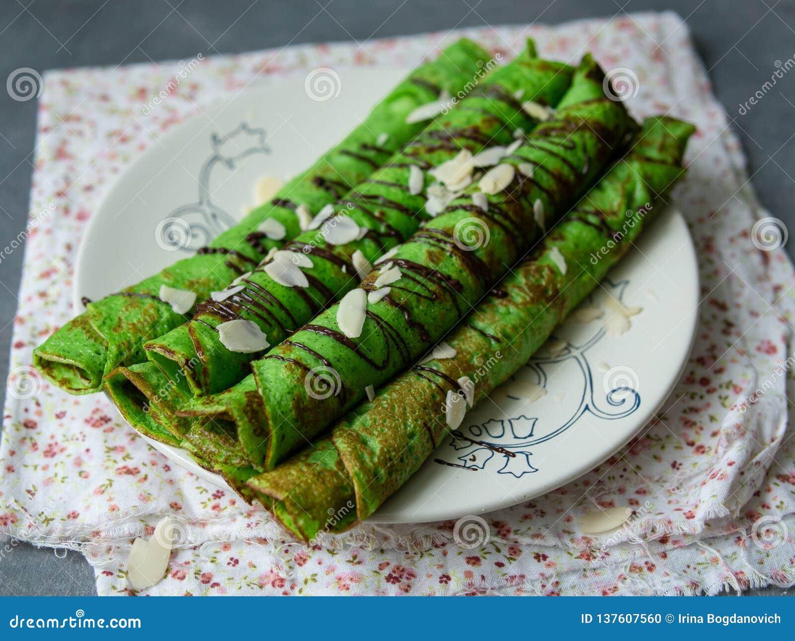 Crepes finos da hortelã da cor verde, torcidos nos tubos, com as pétalas do molho de chocolate e da amêndoa em uma placa branca n