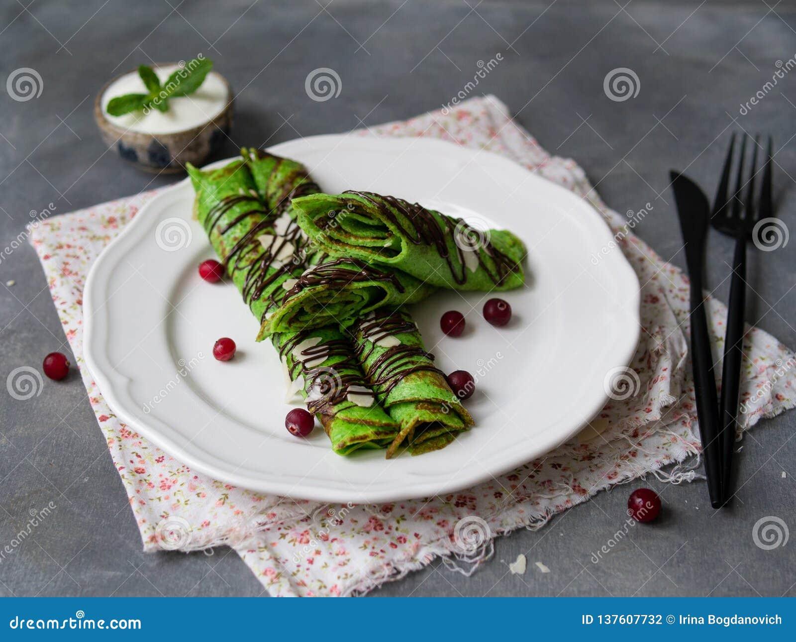 Crepes finos da hortelã da cor verde, torcidos nos tubos, com molho de chocolate, creme de leite, folha da hortelã e pétalas da a