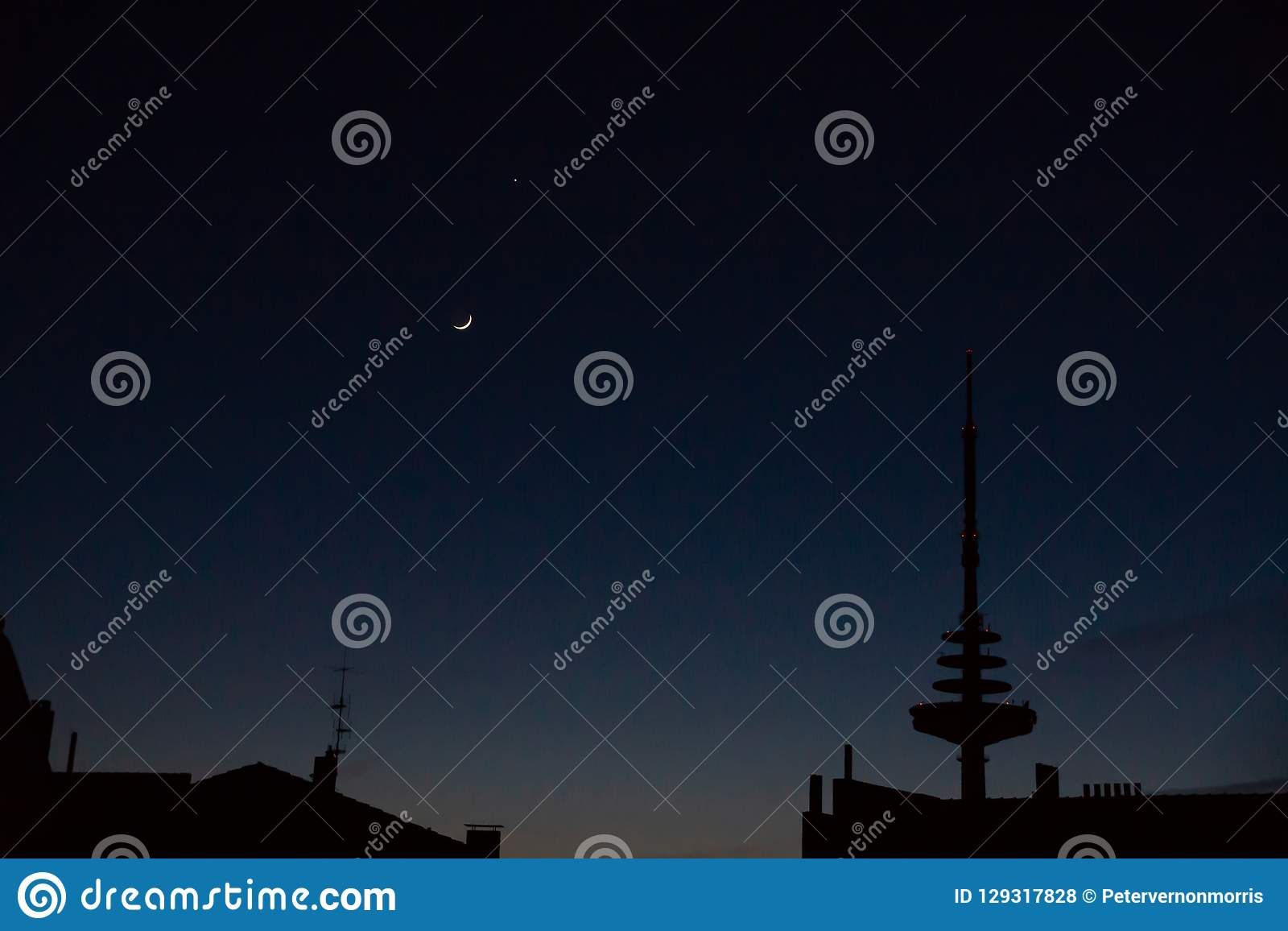 Crescent And Venus On Almost Dark Sky Above City Silhouette