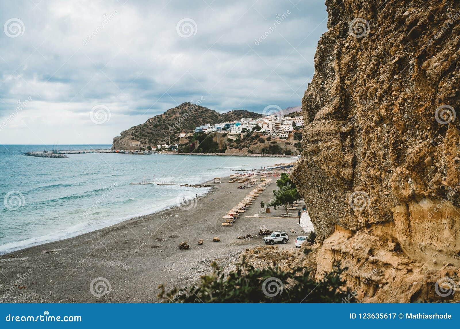 Crete, Grecia Visión desde los acantilados al pueblo con los buques, los barcos y el faro marinos Visión desde el acantilado en b