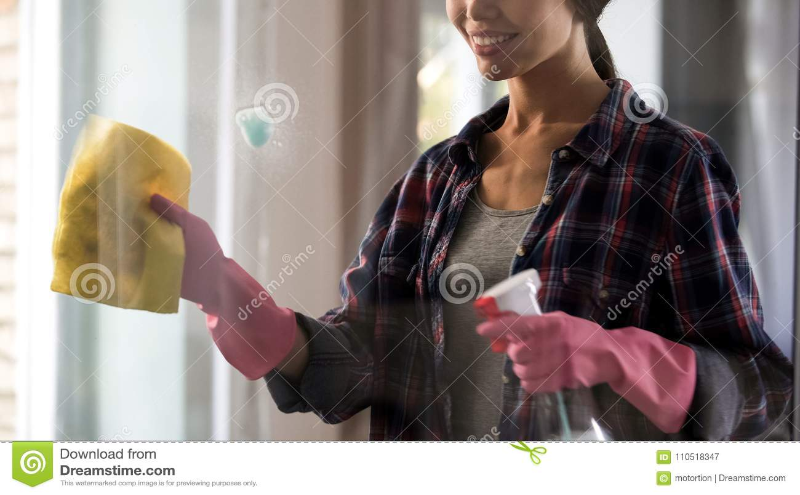 Criada femenina del hotel en los guantes que limpian la ventana de cristal después del espray, eliminación de la mancha