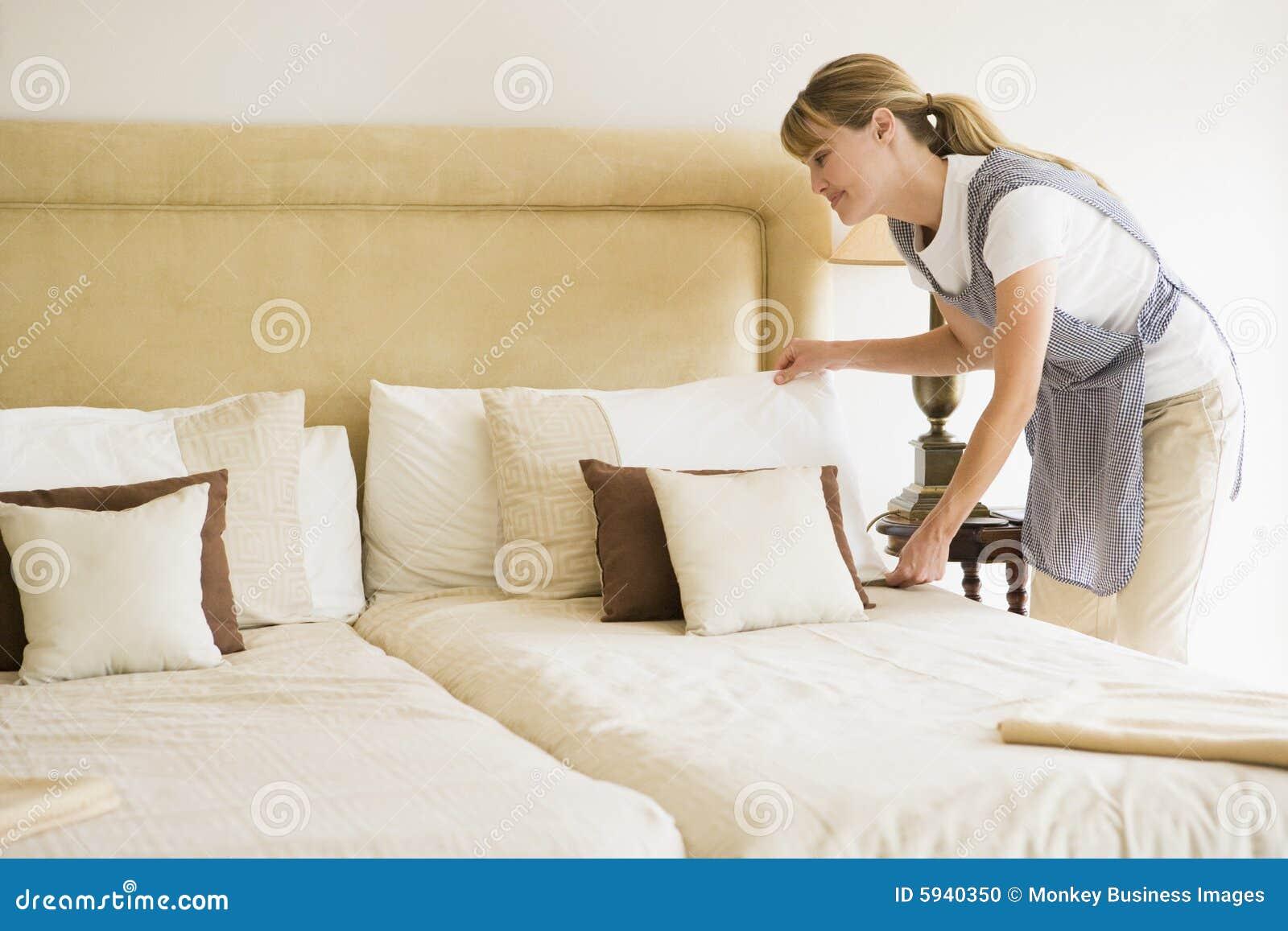Criada que hace la cama en la habitación