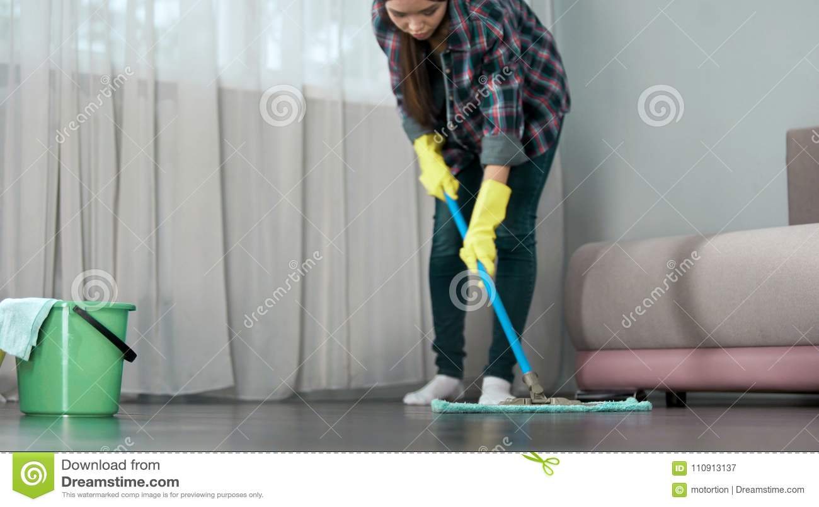 Criada que lava cuidadosamente el piso de la habitación antes de la llegada de huéspedes, limpiando