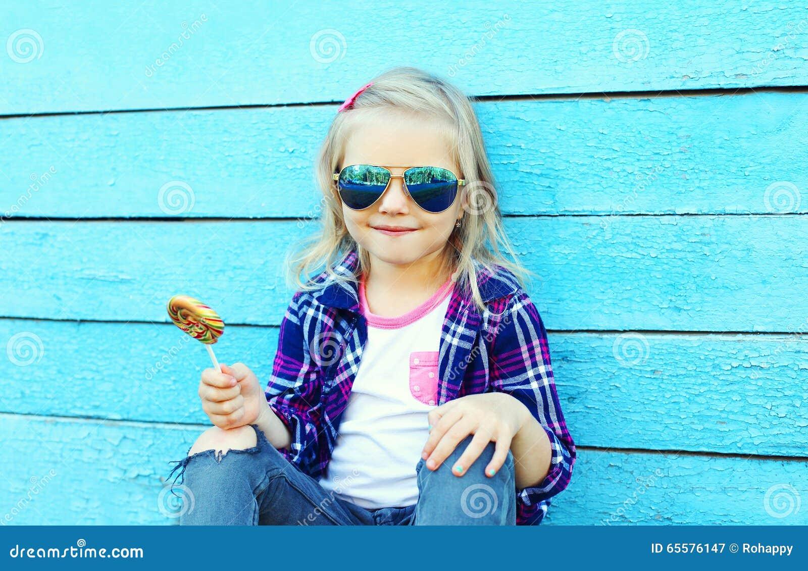 Criança à moda com o pirulito doce do caramelo sobre o azul colorido