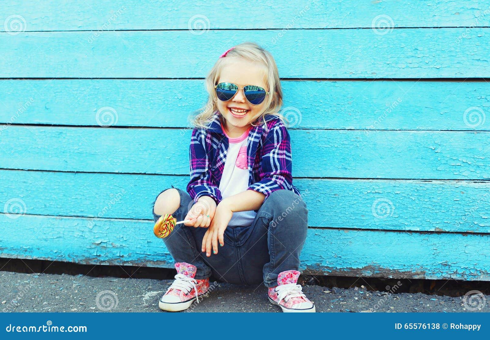 Criança à moda com o pirulito doce na cidade sobre o azul colorido