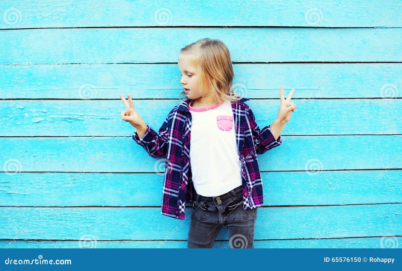 Criança à moda da menina na cidade sobre o azul