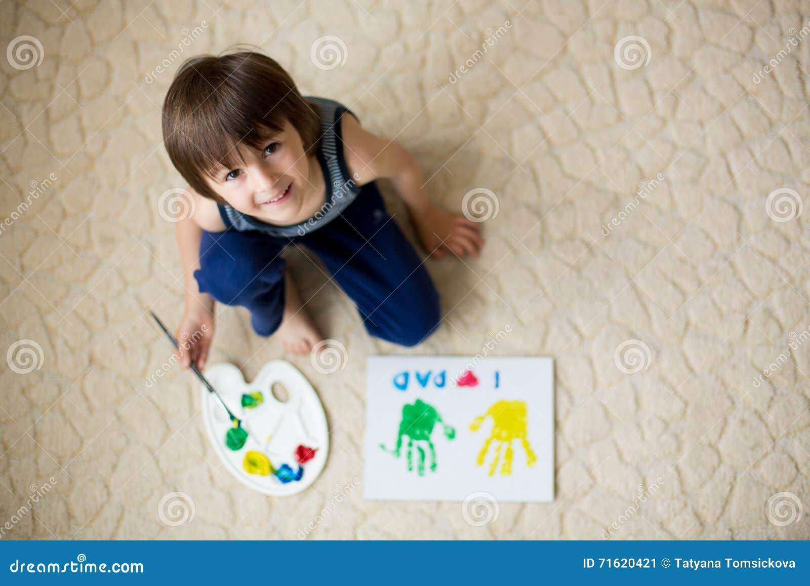 Criança adorável, menino, preparando o presente do dia de pais para o paizinho