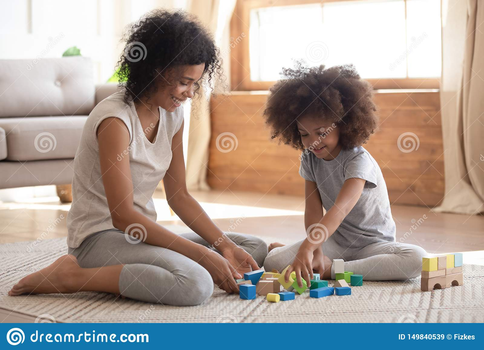 Criança africana pequena bonito que joga com a mamã preta no assoalho