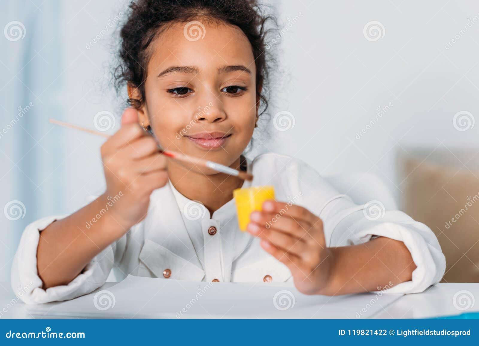 Criança afro-americano adorável que põe a escova de pintura em