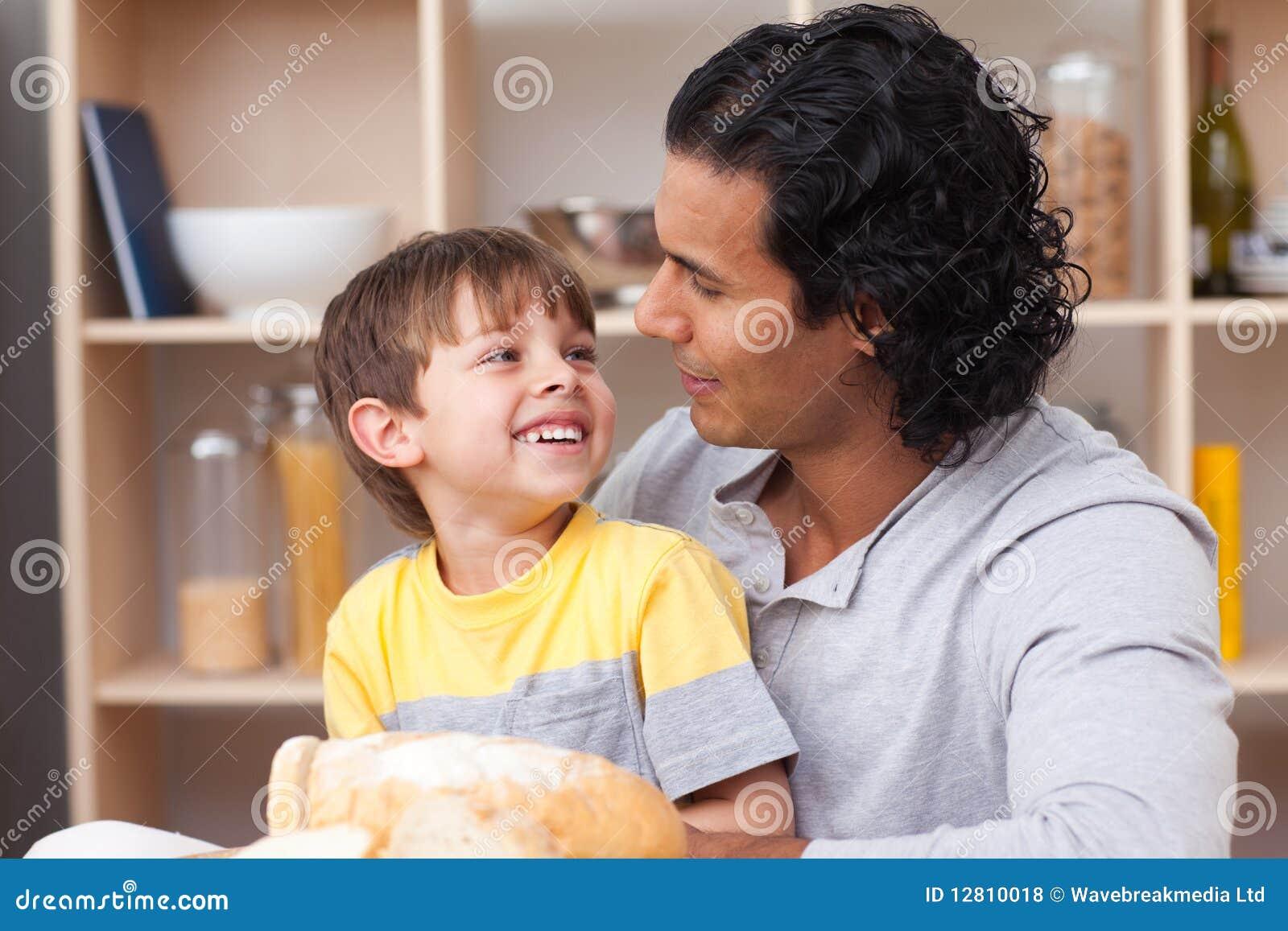 Criança alegre que come o pão com seu pai
