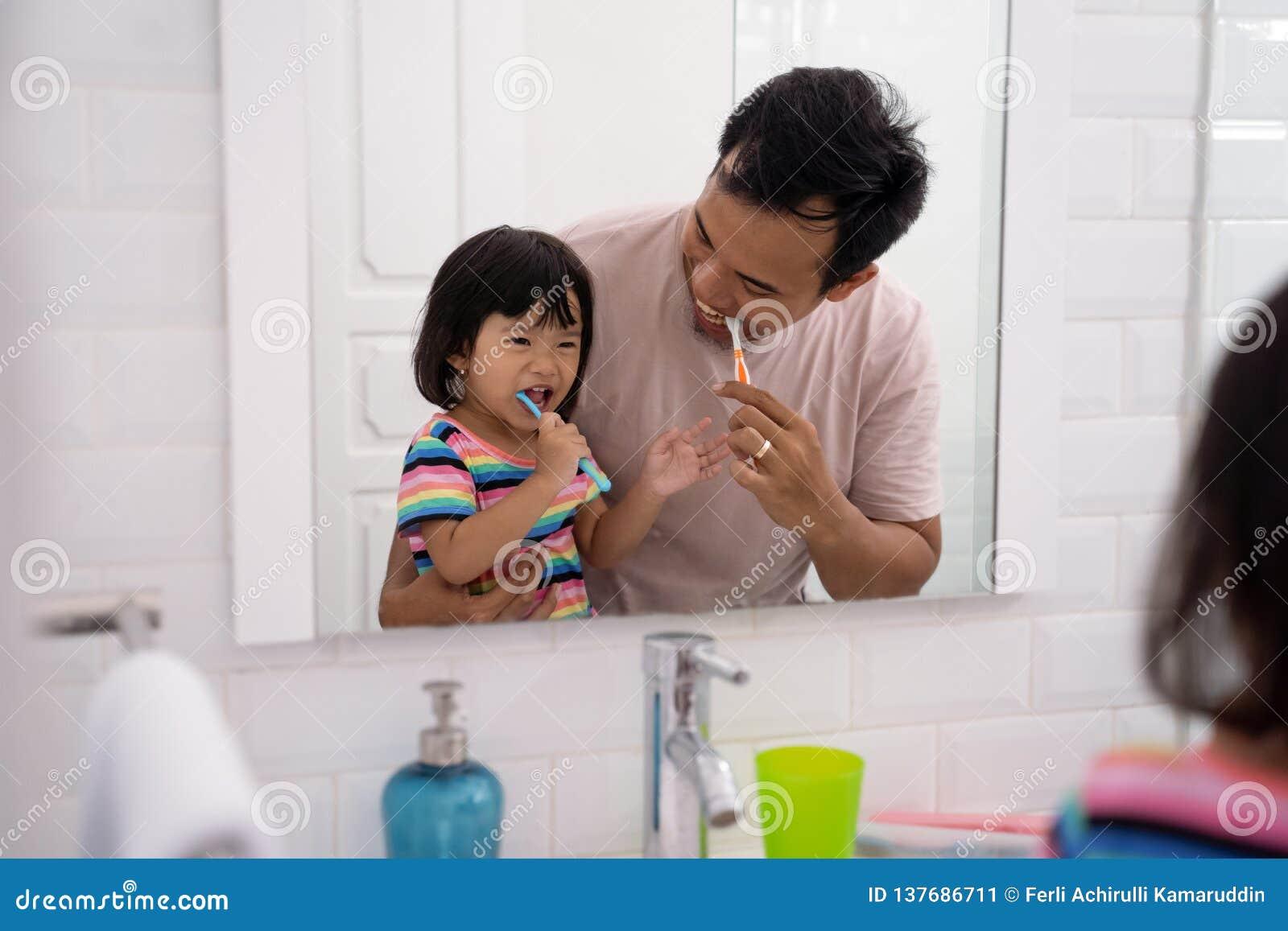 A criança aprende como escovar os dentes com paizinho