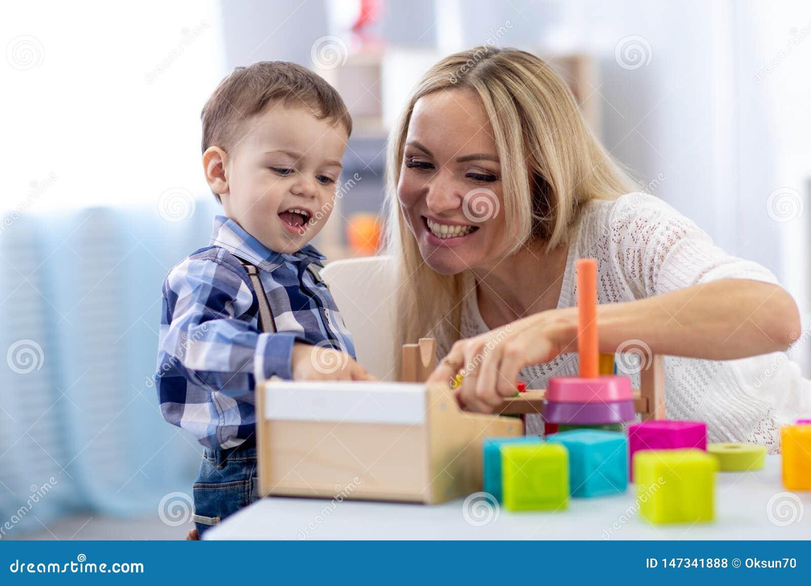 Criança bonito e mãe que jogam com brinquedos em casa Rapaz pequeno que tem o passatempo do divertimento no berçário