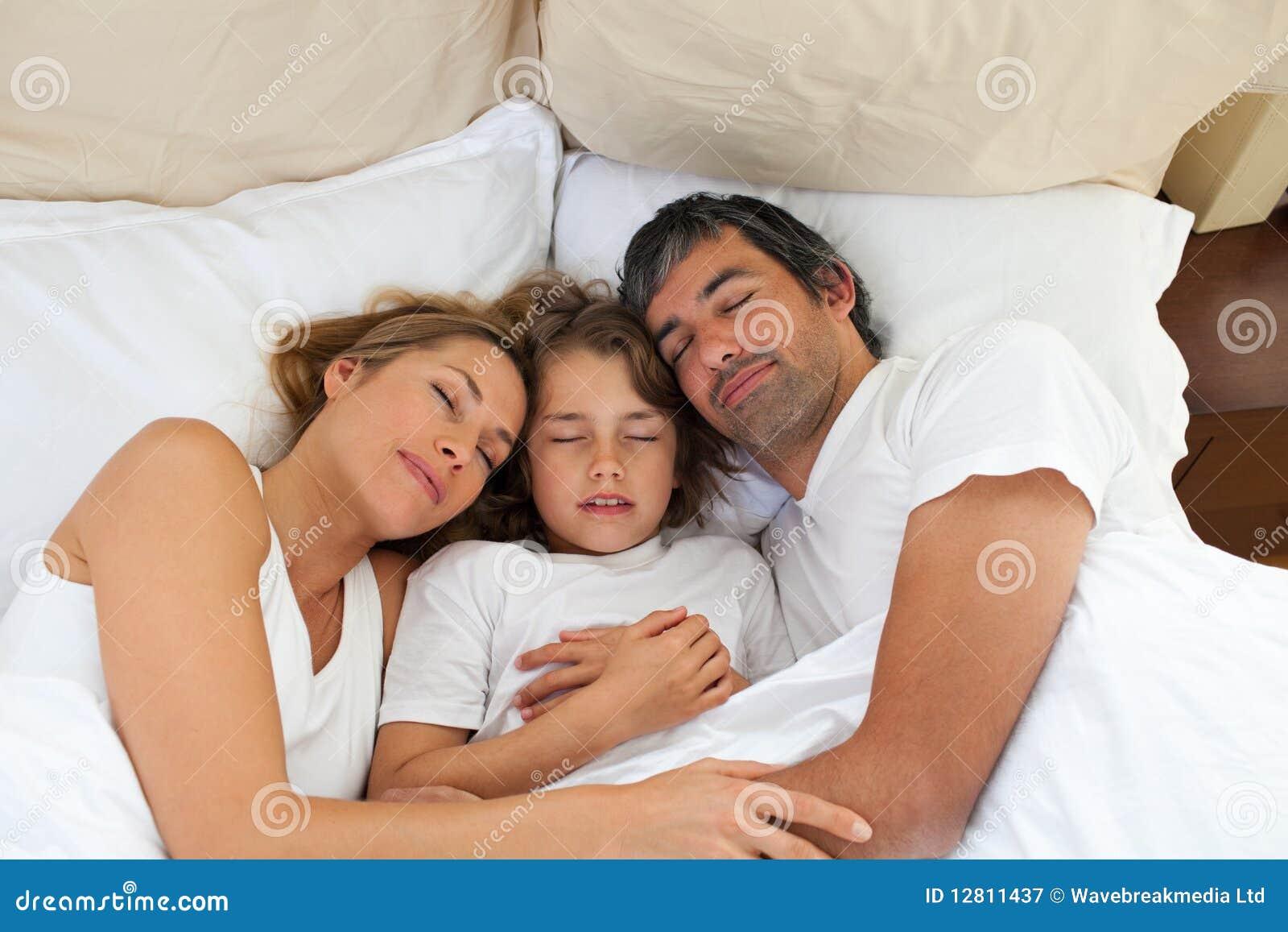 Criança bonito e seus pais que dormem junto