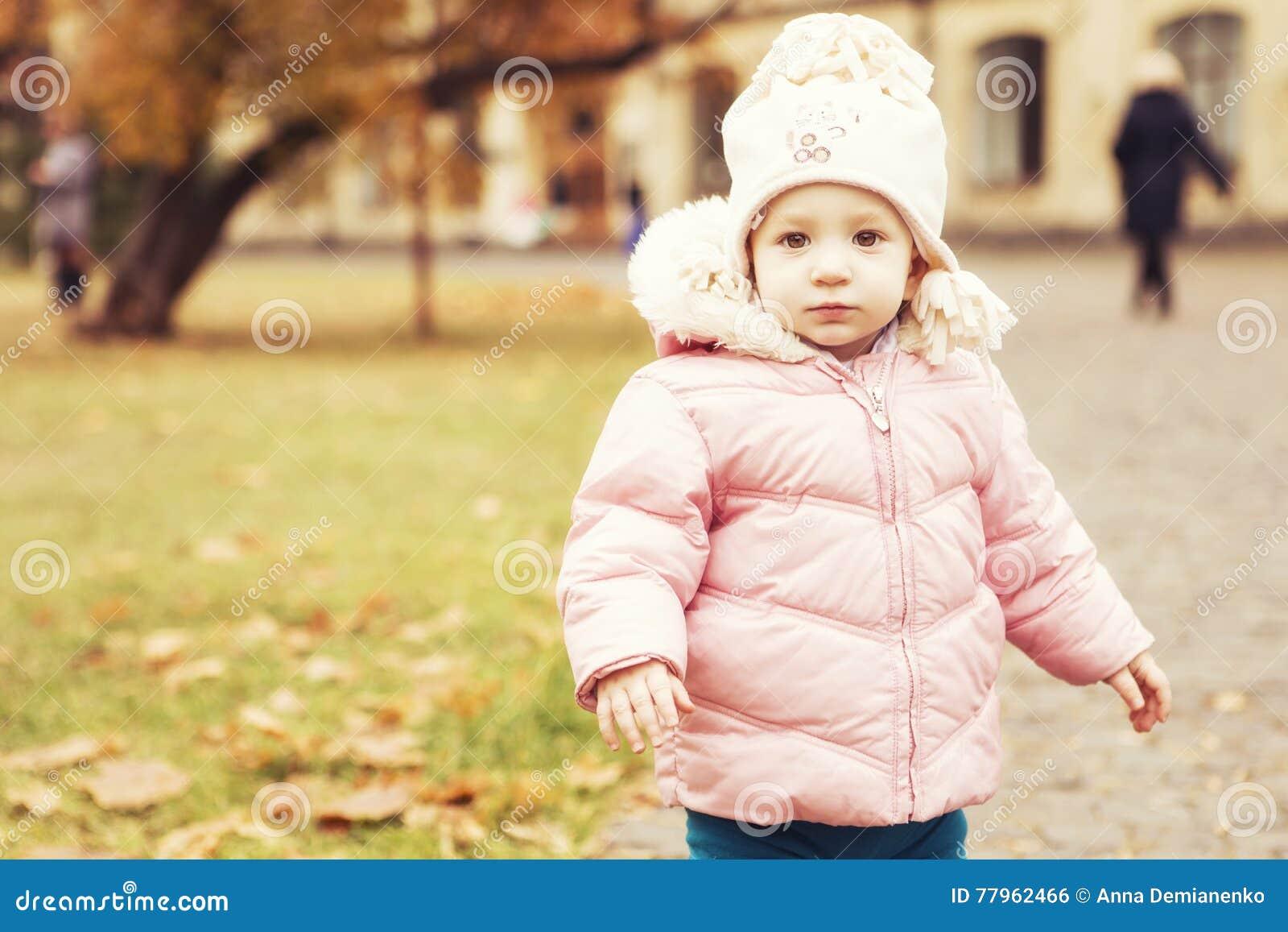 Criança bonito pequena da menina que tem o divertimento no parque na roupa morna do outono & no x28;