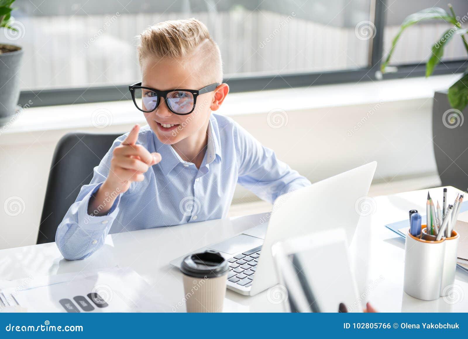 A criança bonito positiva está trabalhando no portátil
