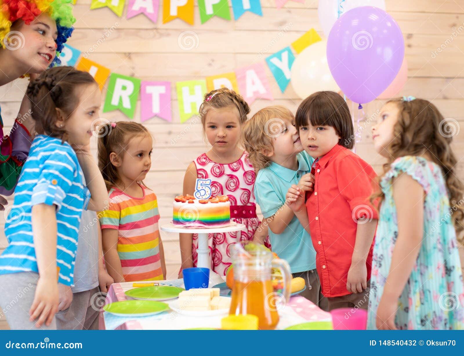 Criança bonito que felicita o menino do aniversário do amigo