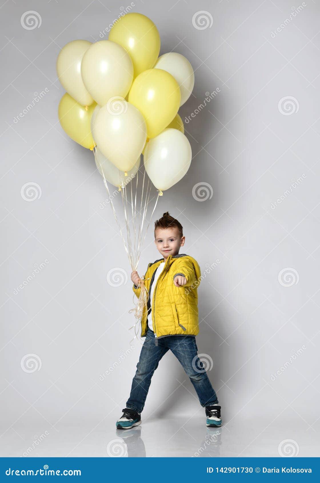 Criança bonito que guarda muitos balões