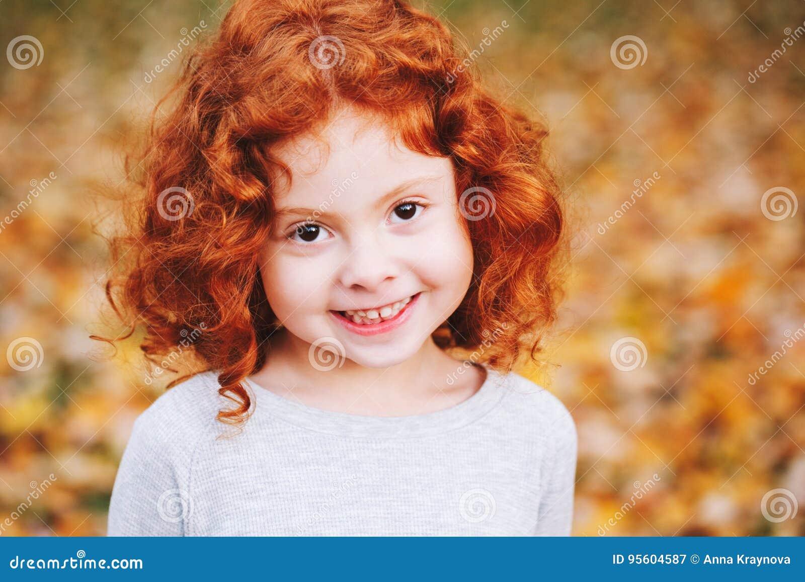 Criança caucasiano ruivo pequena de sorriso adorável bonito da menina que está no parque da queda do outono fora, olhando afastad