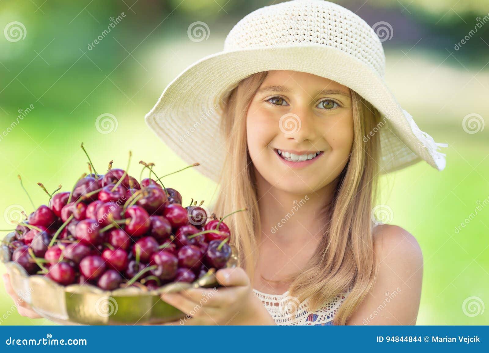 Criança com cerejas Menina com cerejas frescas Retrato de uma moça de sorriso com a bacia completa de cerejas frescas