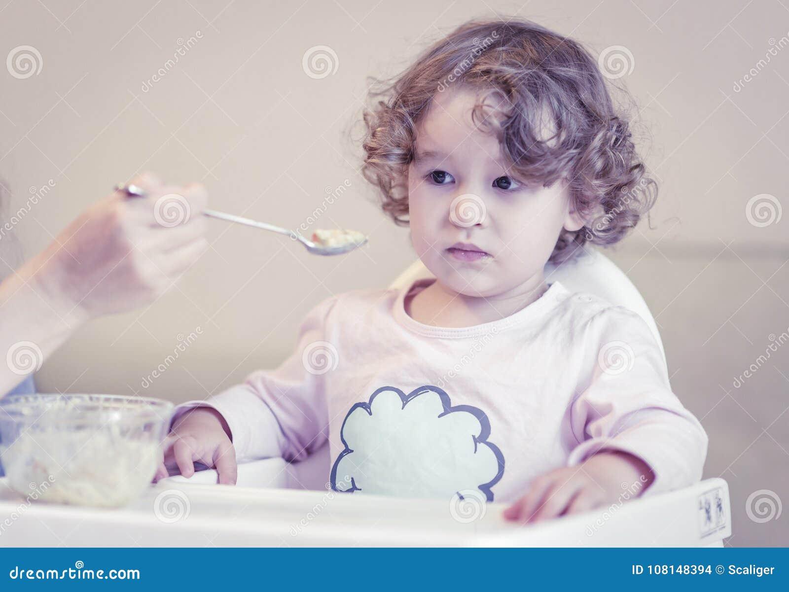 A criança com dois anos come o papa de aveia