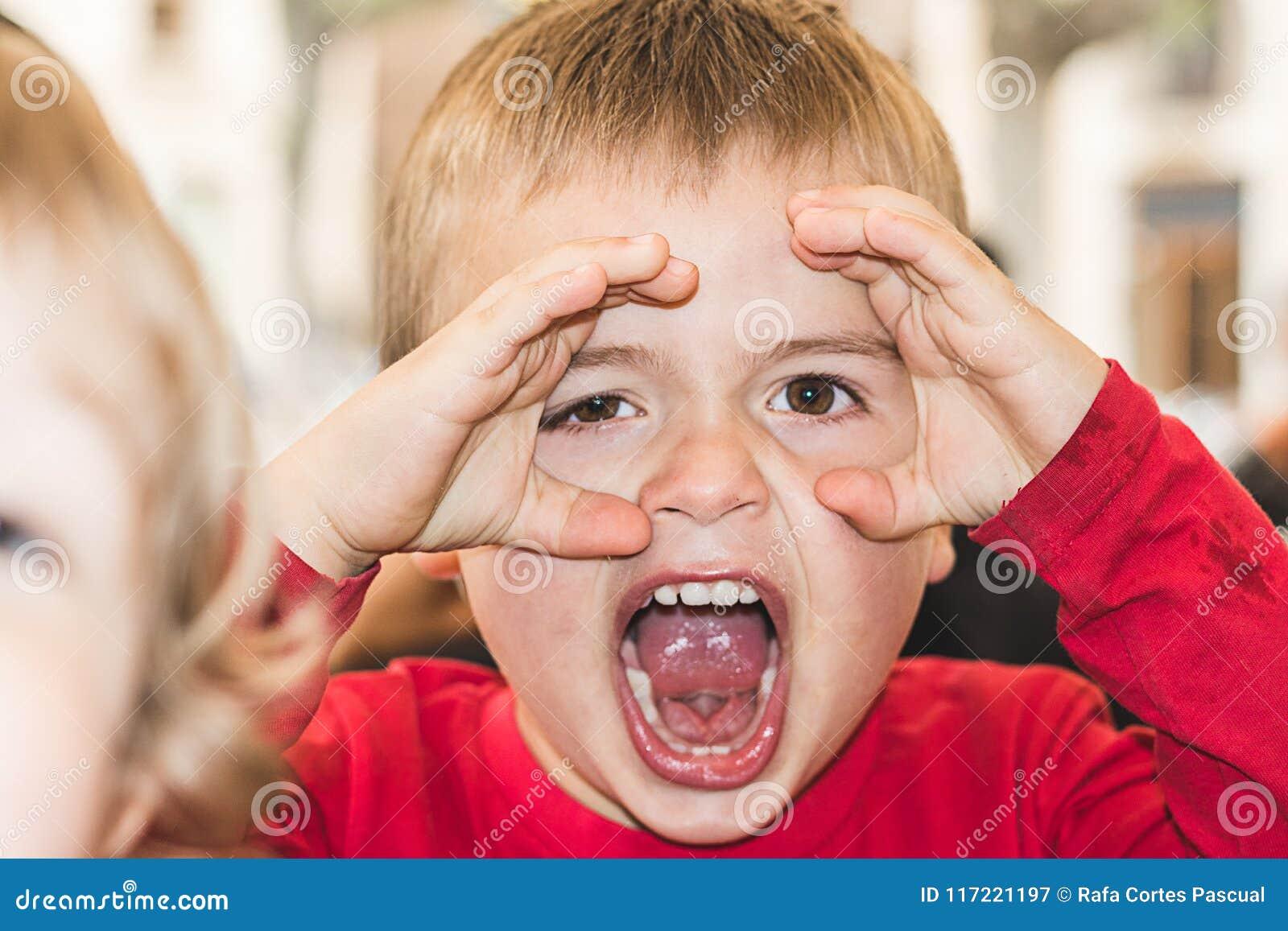 Criança com mãos nos olhos a observar