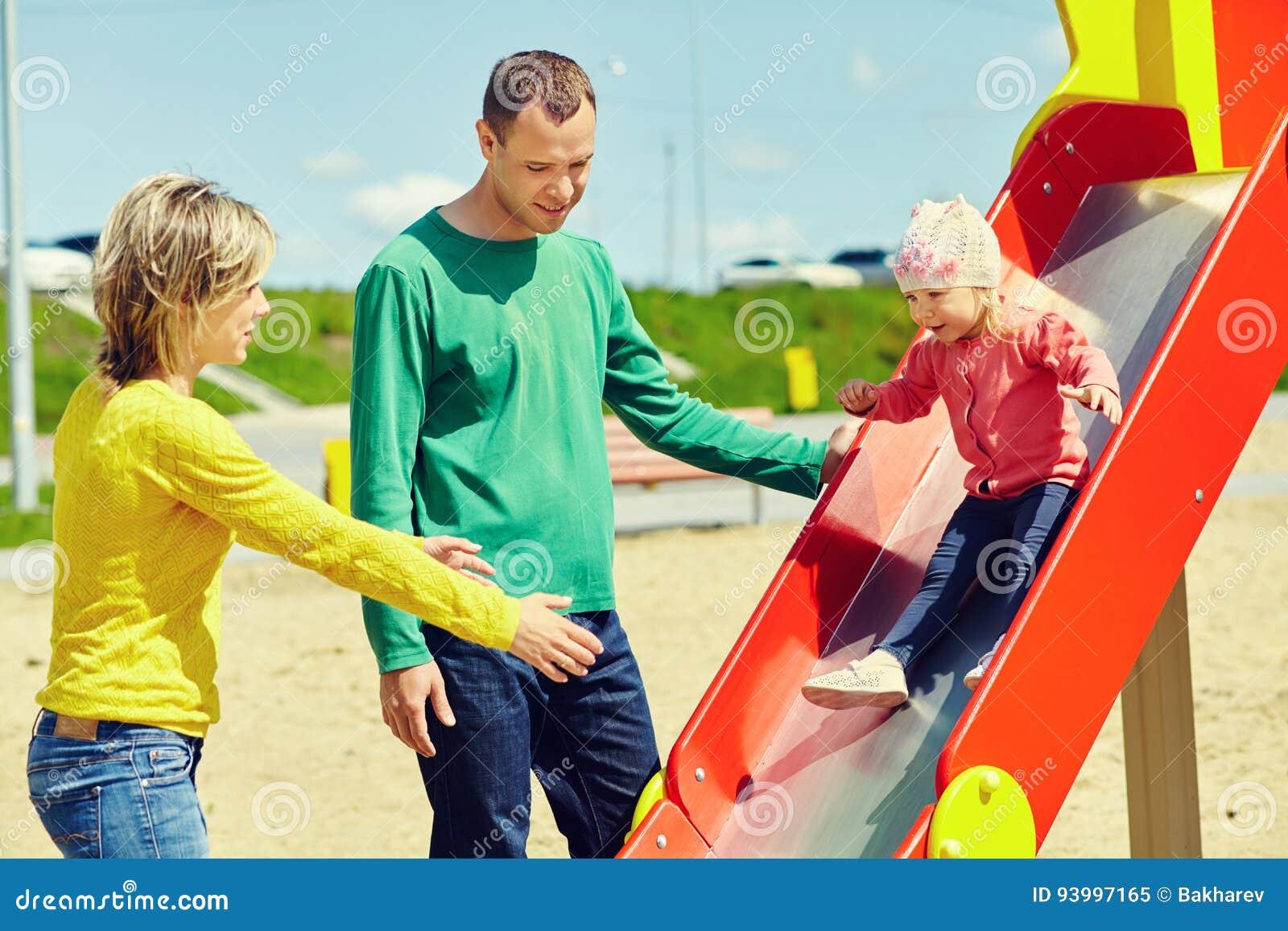Criança com pais em um campo de jogos