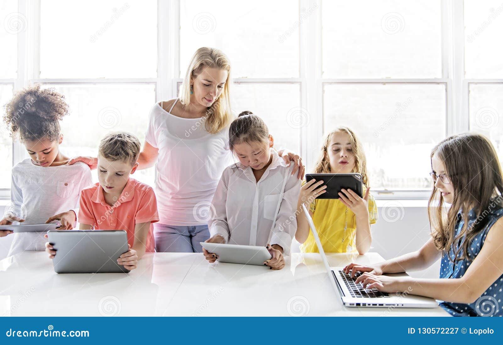 Criança com tabuleta e laptop da tecnologia no professor da sala de aula no fundo